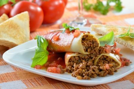 Italiaanse cannelloni gevuld met gehakt en geserveerd met tomatensaus