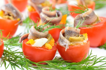 Stuffed cherry tomatoes with anchovies, boiled eggs and green olives photo