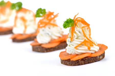 Cheese appetizers  Spiced cream cheese with carrot slices on pumpernickel