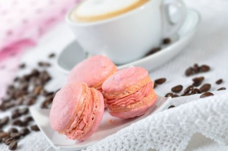 Fine pink macaroons with a cup of cappuccino photo