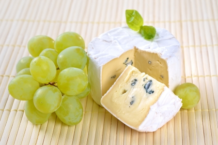 ripened: Ripe blue mould cheese with grapes and basil leaves