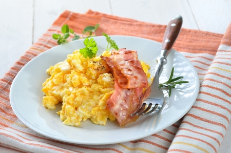 Scrambled eggs with fried bacon photo