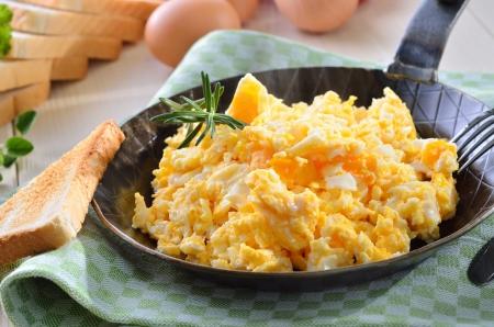 huevos revueltos: Huevos revueltos servidos en un pan con pan tostado