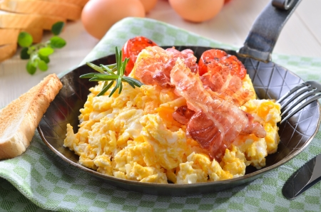 Scrambled eggs with fried bacon served in a pan with toast Standard-Bild