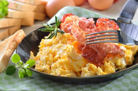 Scrambled eggs with fried bacon served in a pan with toast photo