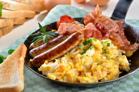 english food: Scrambled eggs with fried bacon and hot sausages
