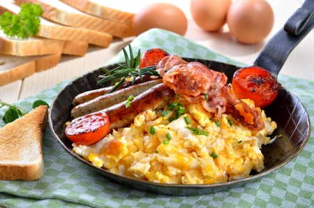 Scrambled eggs with fried bacon and sausages