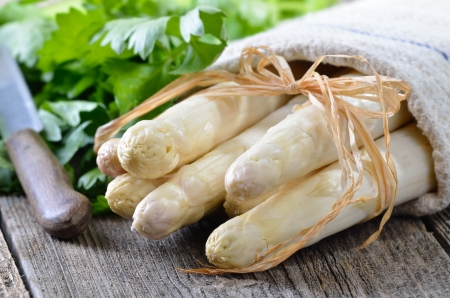 Fresh white asparagus on an old wooden table, celery leaves in the background photo