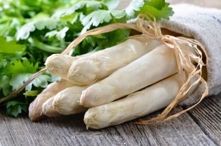 Fresh white asparagus on an old wooden table, celery leaves in the background Standard-Bild
