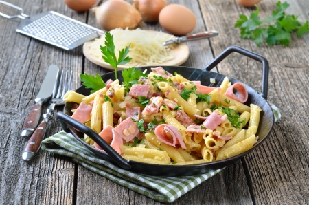 Pasta with ham and bacon, cheese and eggs in a pan Standard-Bild