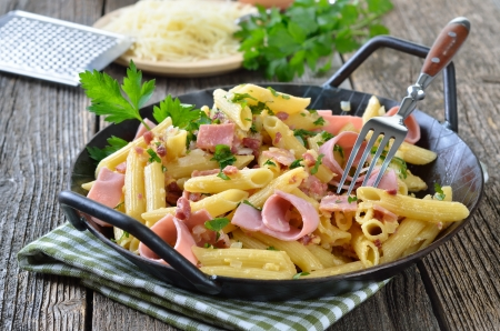 Pasta with ham and bacon, cheese and eggs in a pan Reklamní fotografie