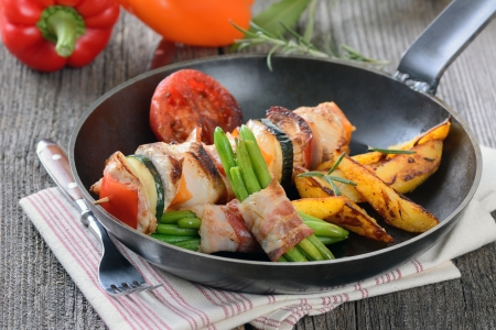 Fried skewer with turkey meat and vegetables, served with green beans wrapped in bacon and roasted potatoes photo
