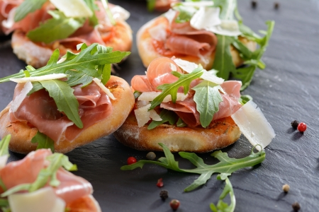Pizza snacks with parma ham, rucola leaves and parmesan cheese Stock Photo