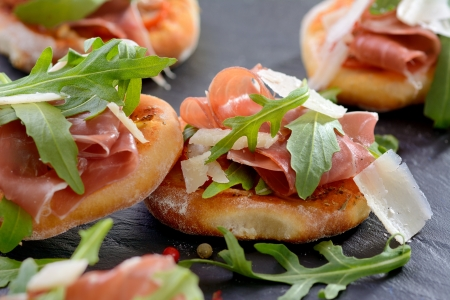 Pizza snacks with parma ham, rucola leaves and parmesan cheese Reklamní fotografie