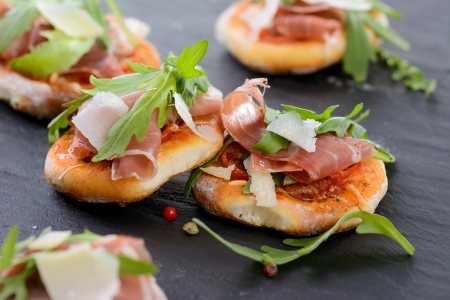 Pizza snacks with parma ham, rucola leaves and parmesan cheese photo