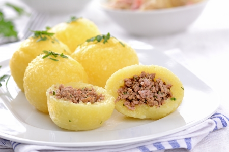 german food: Potato dumplings stuffed with minced meat and served with sauerkraut and bacon Stock Photo