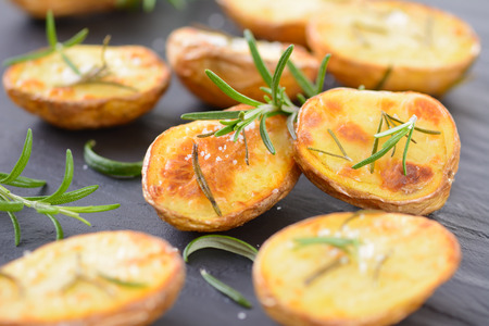 quartered: Baked unpeeled potatoes with rosemary and salt on a slate