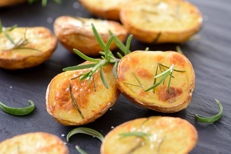 Gebakken ongeschilde aardappelen met rozemarijn en zout op een lei Stockfoto