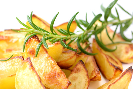 baked potato: Baked potato wedges with rosemary on a white