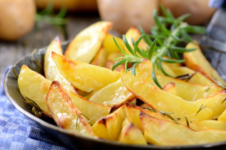 quartered: Baked potato wedges with rosemary in an iron pan
