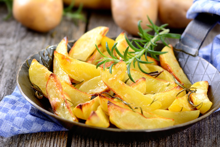 wedges: Baked potato wedges with rosemary in an iron pan
