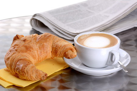 A croissant and a cup of cappuccino photo