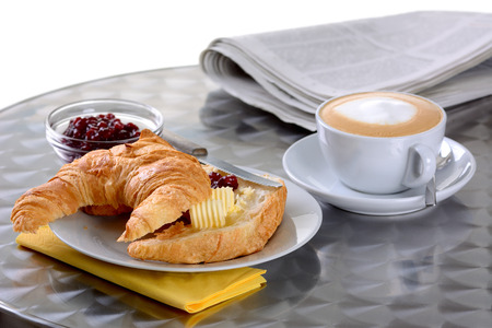 A croissant with butter and jam and a cup of cappuccino photo