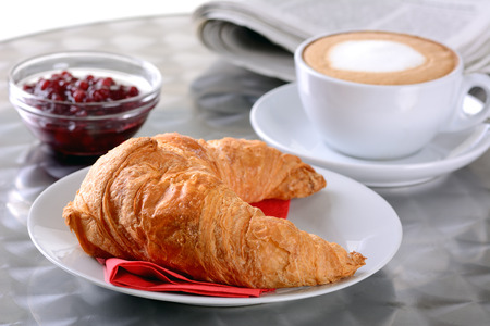 Croissant and a cup of cappuccino photo