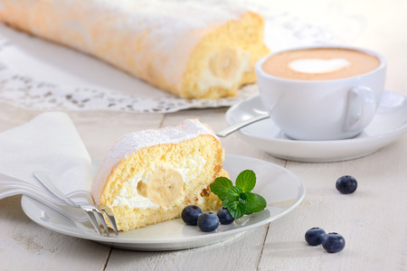 Swiss roll stuffed with banana and cream, a cup of cappuccino in the background photo