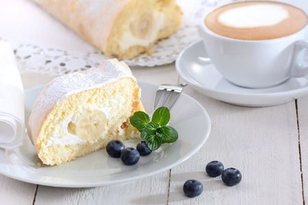 roulade: Swiss roll stuffed with banana and cream, a cup of cappuccino in the background