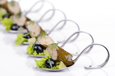 Stuffed grape leaves with black olives on appetizer spoons Reklamní fotografie