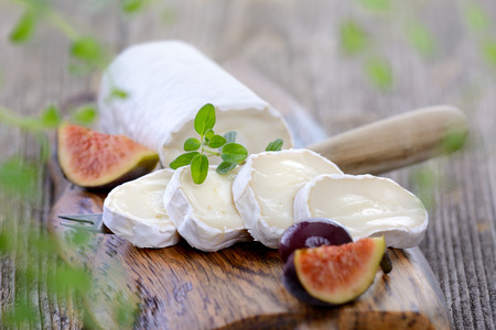 Goat cheese with figs and black olives on a wooden cutting board