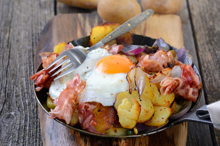 Hearty breakfast with fried potatoes, egg and bacon