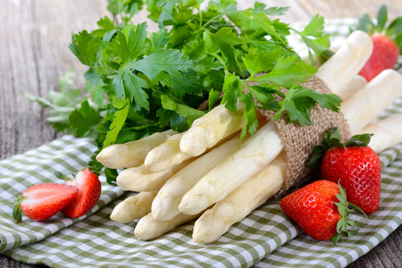 White asparagus from Germany with strawberries on a wooden table