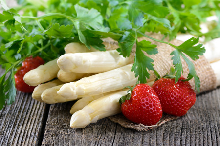White asparagus from Germany with strawberries on a wooden table photo