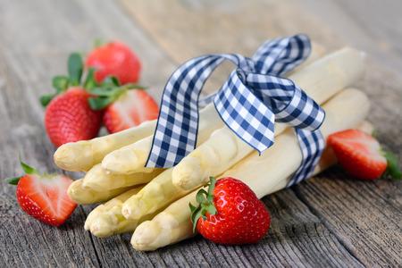 Bílý chřest z Německa s jahodami na dřevěný stůl Reklamní fotografie