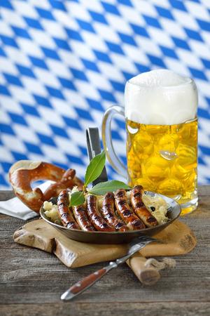 Fried Nuremberg sausages on sauerkraut with a mug of beer Bavarian Reklamní fotografie