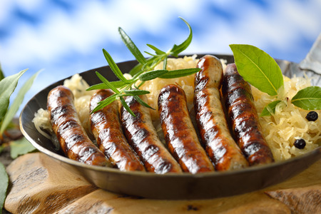 Bavarian fried sausages on sauerkraut served in a frying pan