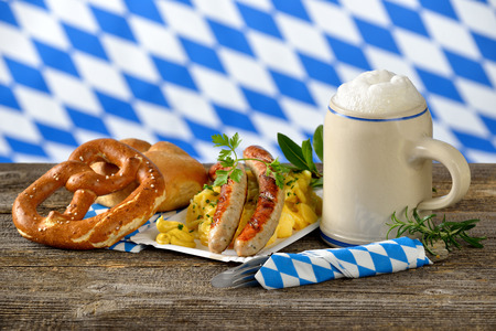 Fried Bavarian sausages on potato salad served with pretzels and Bavarian beer in a tankard