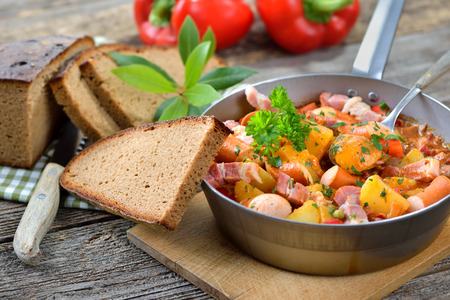 stew pan: Hot potato goulash with bacon and sausages served in Vienna on iron pan with delicious dark baked farmhouse bread