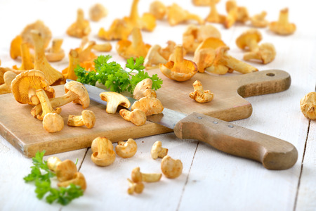 girolle: Fresh chanterelles with a wooden cutting board and a kitchen knife on a rustic white table