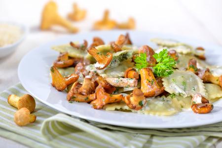 Italské ravioli s čerstvými restovanými liškami a parmazánem krémová sýrovou omáčkou Reklamní fotografie