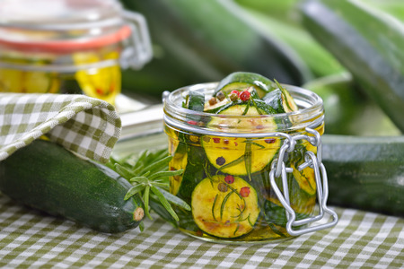 Fried zucchini slices pickled in olive oil with herbs and filled in a canning jar
