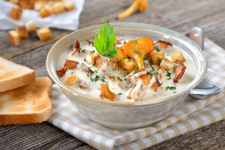 Delicious cream soup with fried chanterelles, croutons and toast