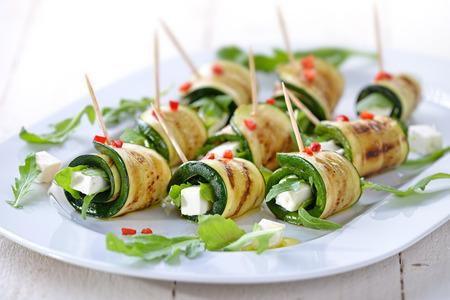 calabacin: deliciosos rollos de rodajas de calabacín frito y queso feta con rúcula, servido con aceite de oliva y trozos de pimientos