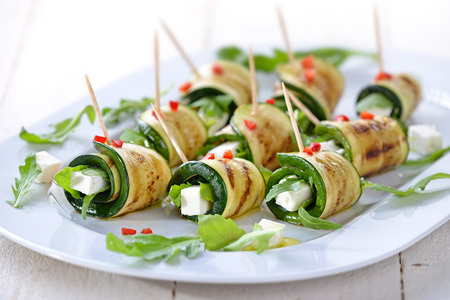 Delicious rolls of fried zucchini slices and feta cheese with arugula, served with olive oil and pieces of bell peppers