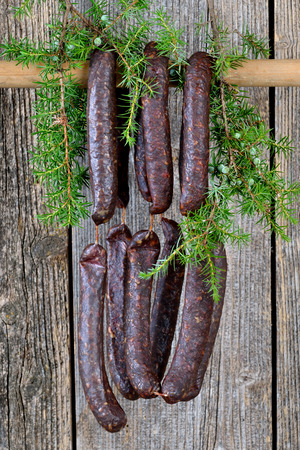 air dried salami: Cured sausages from South Tyrol with juniper branches