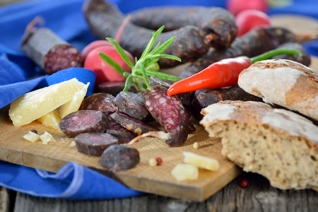 air dried: Typical snack from South Tyrol: dark smoked and air dried sausages with rye flatbread Stock Photo
