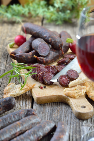 wine and dine: South Tyrolean snack with typical cured sausages and very crispy flatbread, served with a glass of red wine
