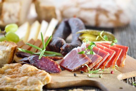 carnes: Merienda abundante del Tirol del Sur con tocino, queso de montaña picante, embutidos y pan Foto de archivo